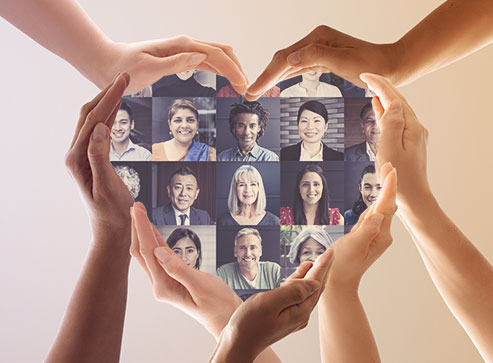 Hands forming the shape of a heart with headshot images of people in the middle.
