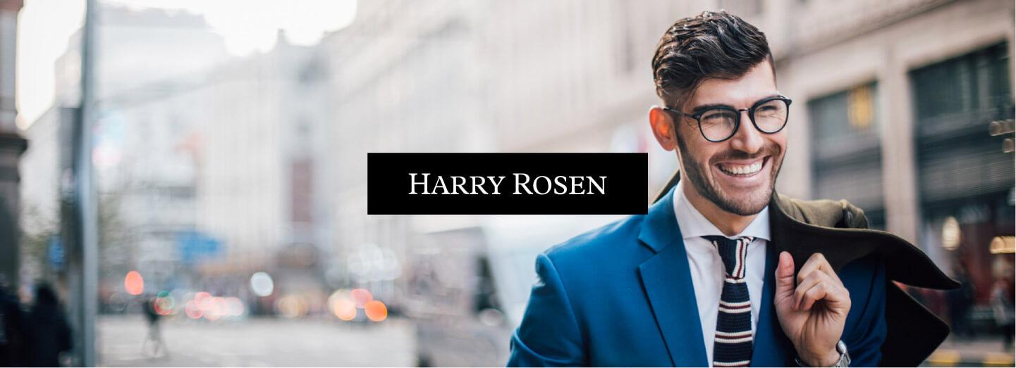 smiling man with jacket over shoulder and harry rosen logo