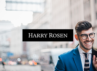 smiling man with jacket over shoulder and harry rosen logo