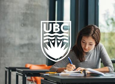 Young woman studying on a campus bench at UBC