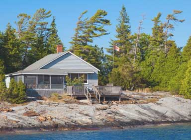 small-cottage-on-lake-with-canadian-flag