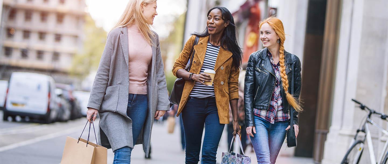 Millennial women shopping on urban retail street