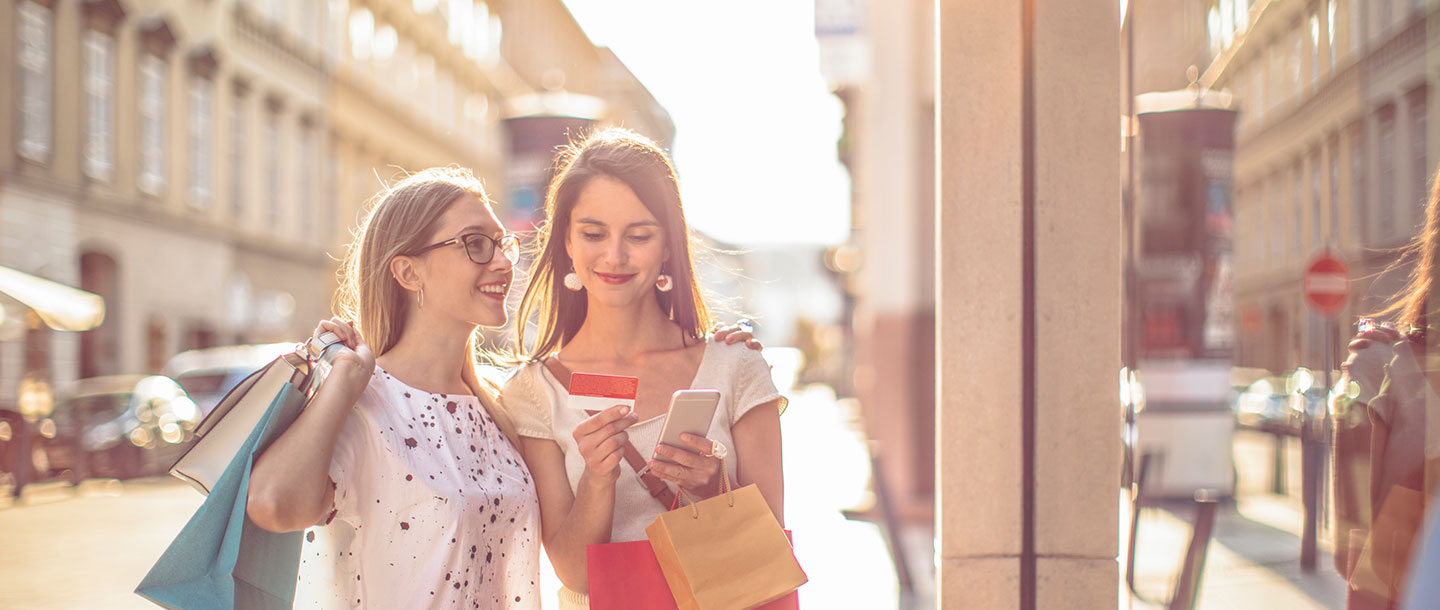 Millennial women buying goods with mobile phones