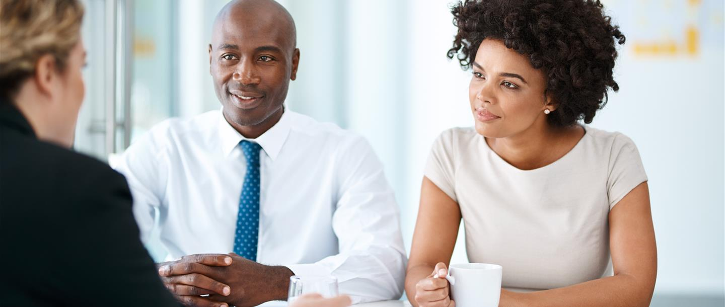 Advisor talking to a millennial couple on financial investment behaviour