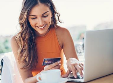 Millennial woman using laptop and credit card for online shopping