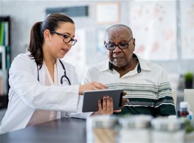 Female physician shows a wellness program to an elderly man