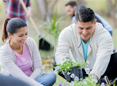 Young couple planting flowers for charity