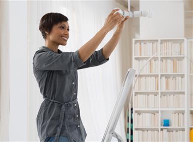 Millennial woman changing energy efficient lightbulbs