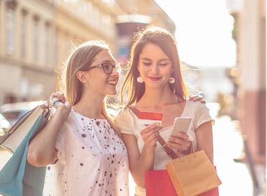 Mobile devices being used by millennial women to shop