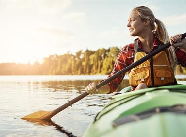 Millennial woman kayaking in stunning natural location