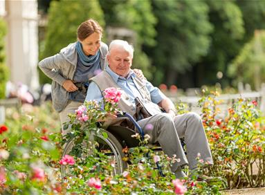 Caregiver and elderly man in community garden